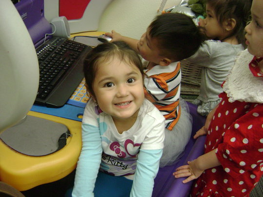 Preschoolers play learning games on computers
