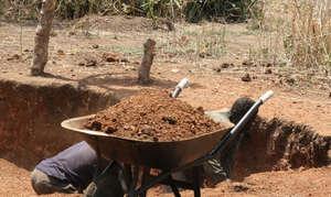 Omilling, a wheelbarrow full red soil marram