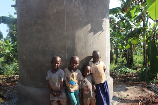 children leaning on a water tank