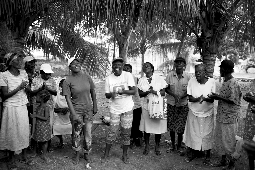 """Haitian women singing and clapping as they mark the beginning of a meeting to discuss plans for rebuilding after the earthquake. Photo by Roberto """"""""Bear"""""""" Guerra"""