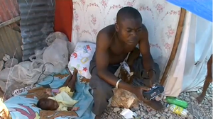 Haitian Father Listens to News on Surivival