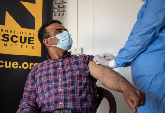 A Syrian refugee proudly receives his vaccine