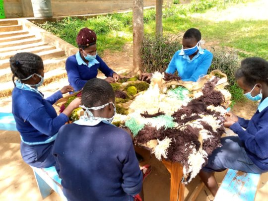 Students learning how to make mats outside