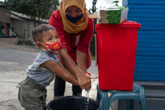 Mother washes her child's hands in Indonesia