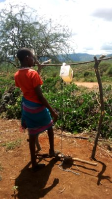 A youth using a handwashing station set up by CORP