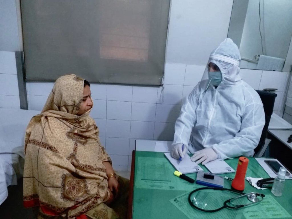 Doctor examining patient, using full protection