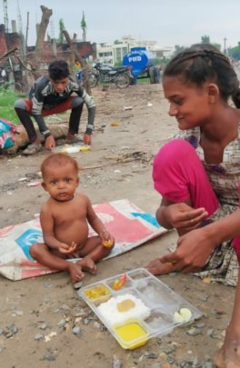 Feeding nutritious meal to a child in slum