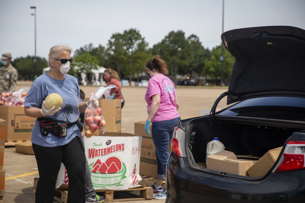 Volunteers loading trunk with produce