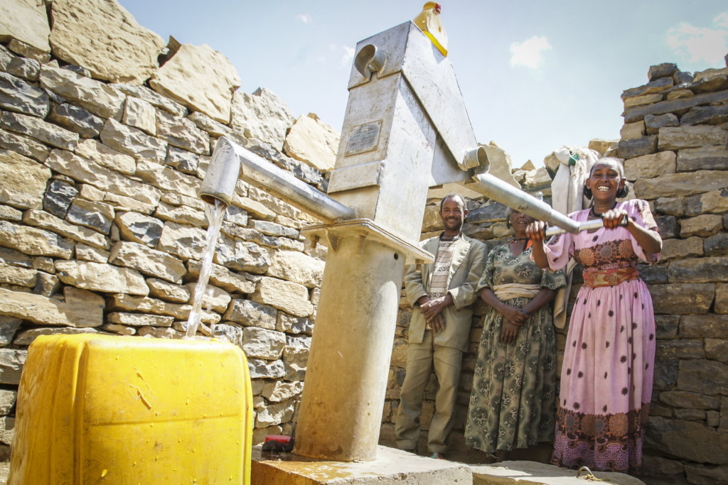Woman pumping water from Drop of Water well
