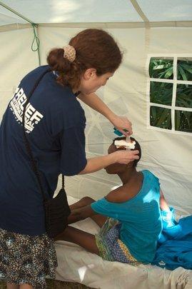 Dr. Orna Hananel treats a patient's head wound.