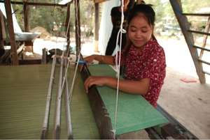 Vannah oversees a worker at a weaving loom