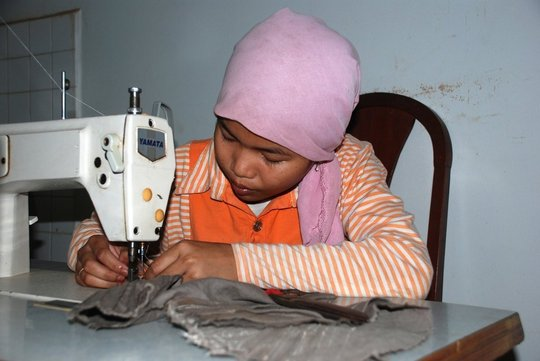 A young girl learning sewing skills