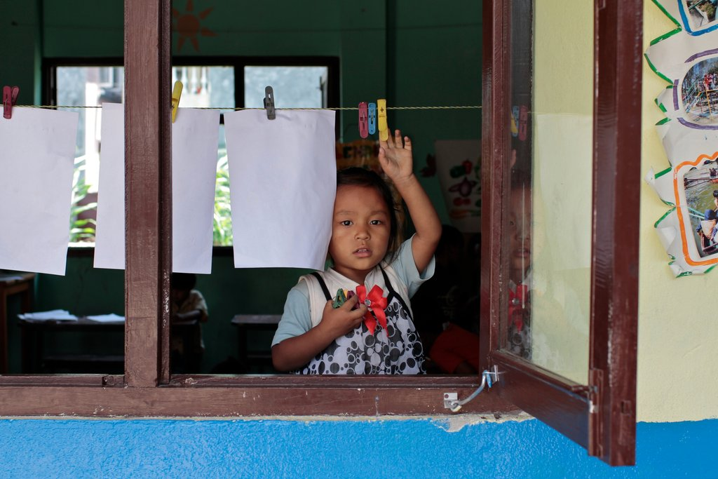 A girl at Orchid Garden Nepal hanging up her artwork in the classroom.