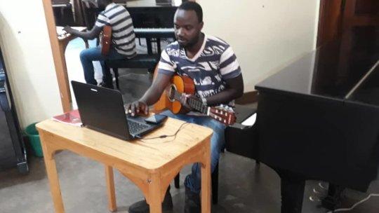 Teacher George delivering an online guitar lesson