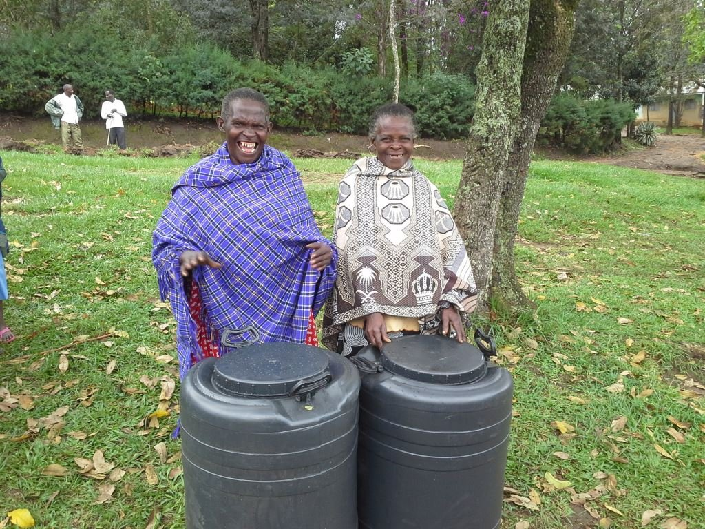 Two grandmothers with water harvesting tanks