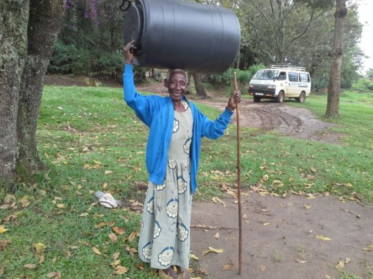 Grandmother holding a water harvesting tank