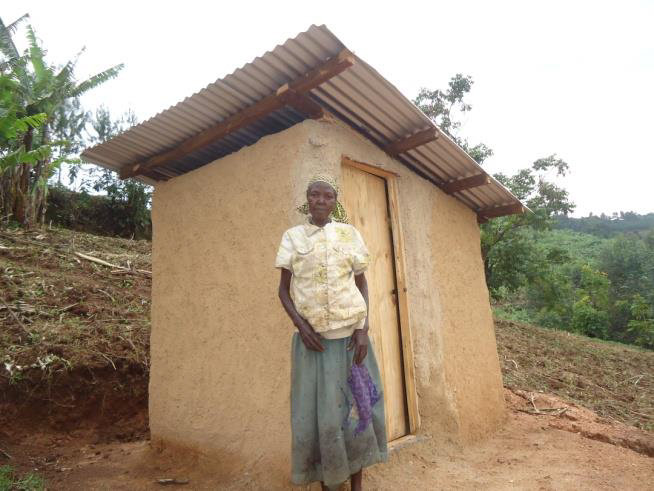 Consirantah in front of her new pit latrine