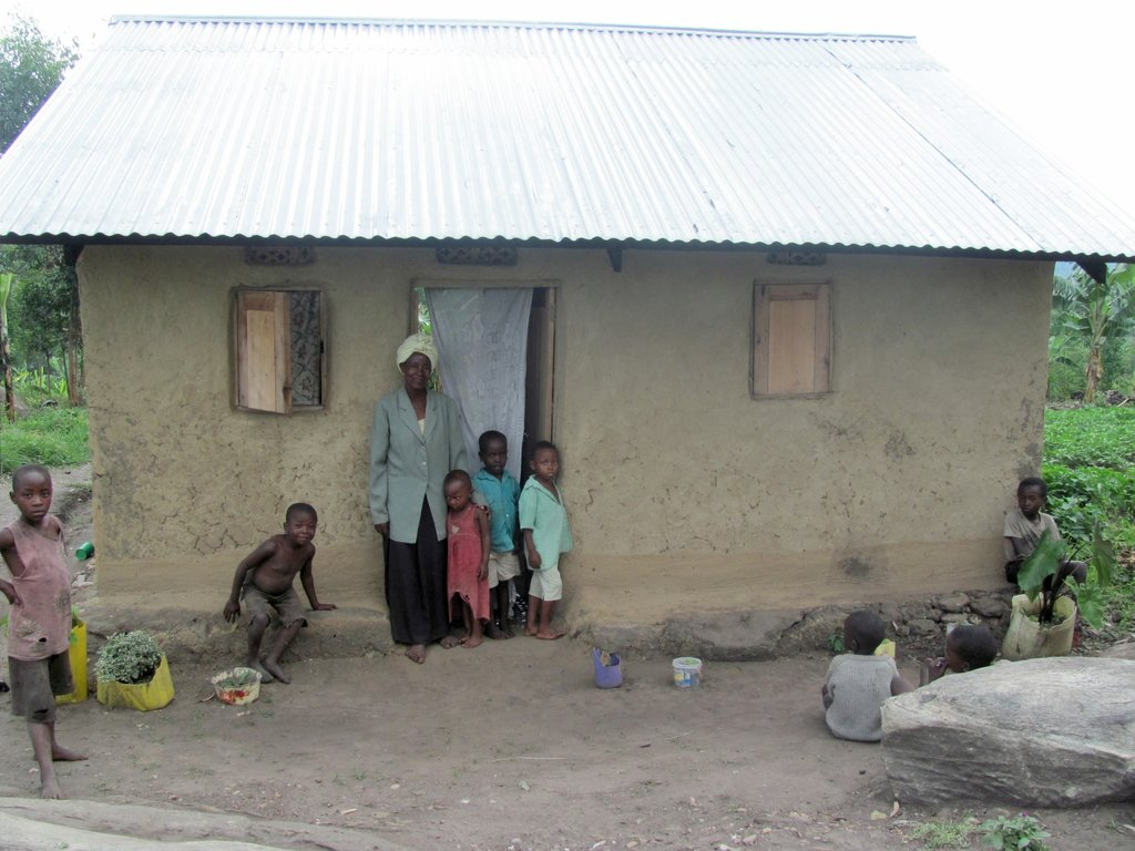A grandmother and children next to home.
