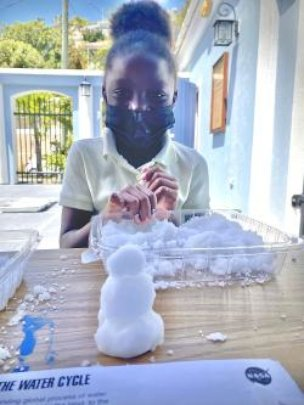 A child builds a snowman with polymer snow