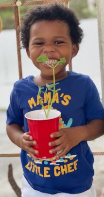 A child shows off the plant he grew with DK5 items