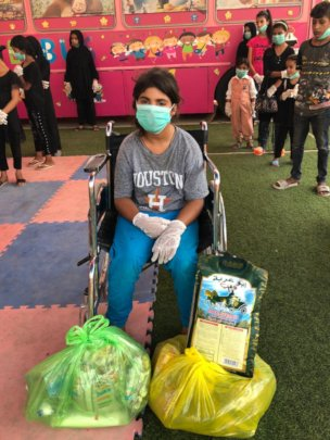A Hope Bus student in a wheelchair gets packages