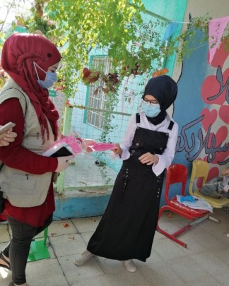 Distributing masks made by low-income women & moms