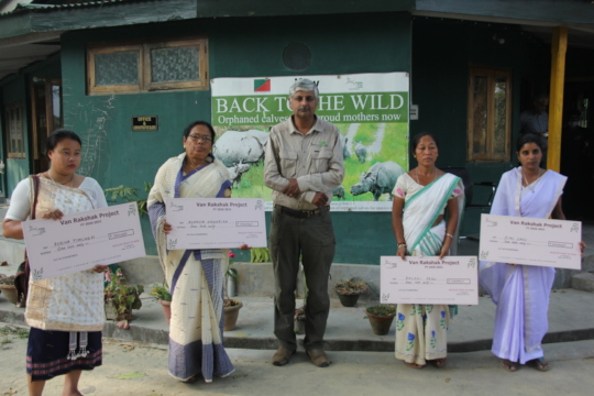 Handing over cheques to families of Forest staff.