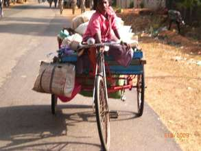 Girl child riding tri-cycle load of waste paper