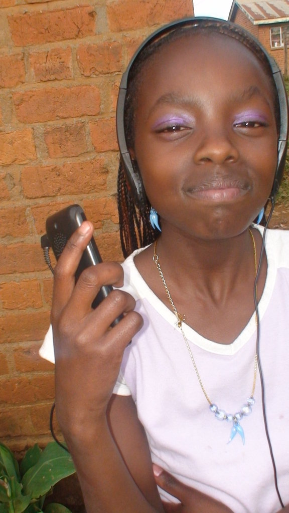 A young girl listens to a HIV/Aids message using an I-pod during a sensitization campaign conducted by GEMINI.