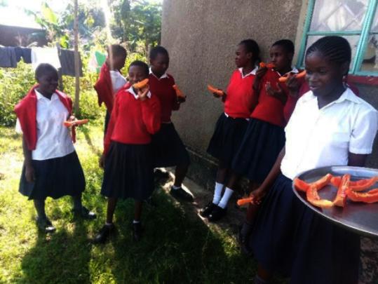 Girls enjoying papaya from school farm
