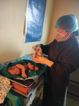A PHASE Staff attending a neonate after delivery