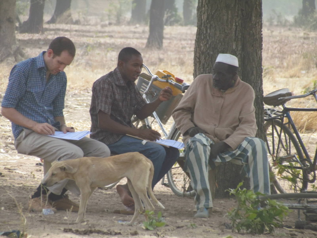 Two BARKA staffers interview a villager