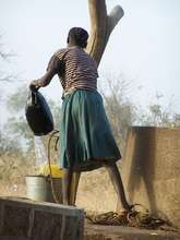 Bual Hamu pours dirty water from an open well.