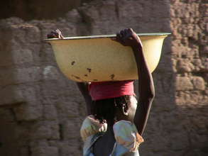 Young girl carries heavy basin of water.