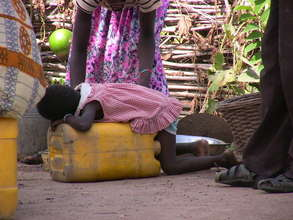 Little girl exhausted and asleep on a jerry can.