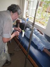 A medical team member in October starting an IV