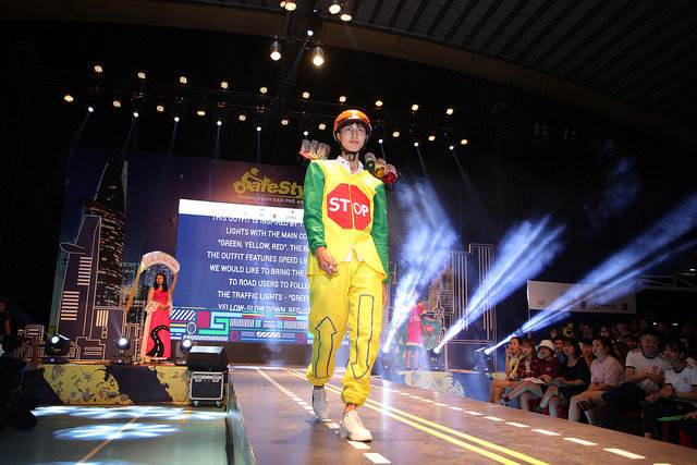 Students in road safety outfits walk the runway.