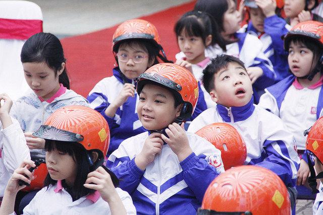 A student follows a helmet-wearing demonstration.