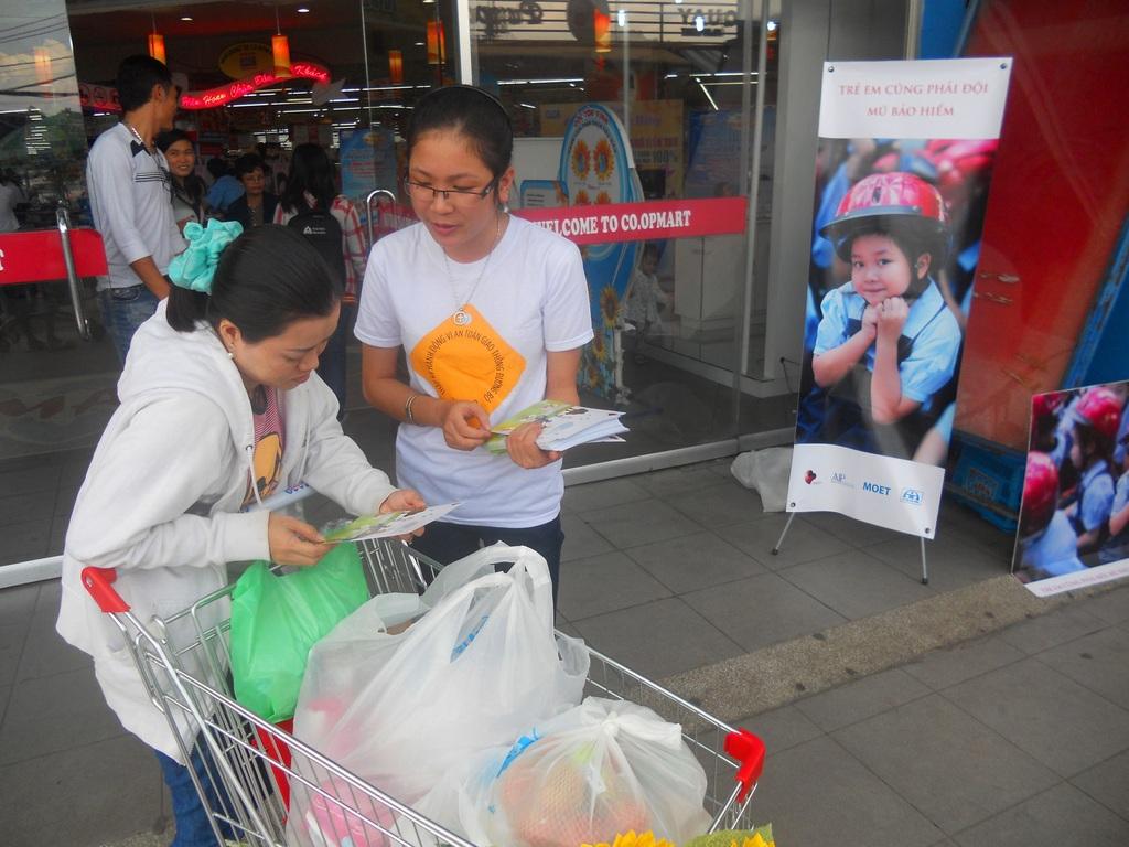 Distributing flyers outside a supermarket