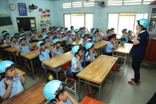 A volunteer teaches students how to wear helmets.