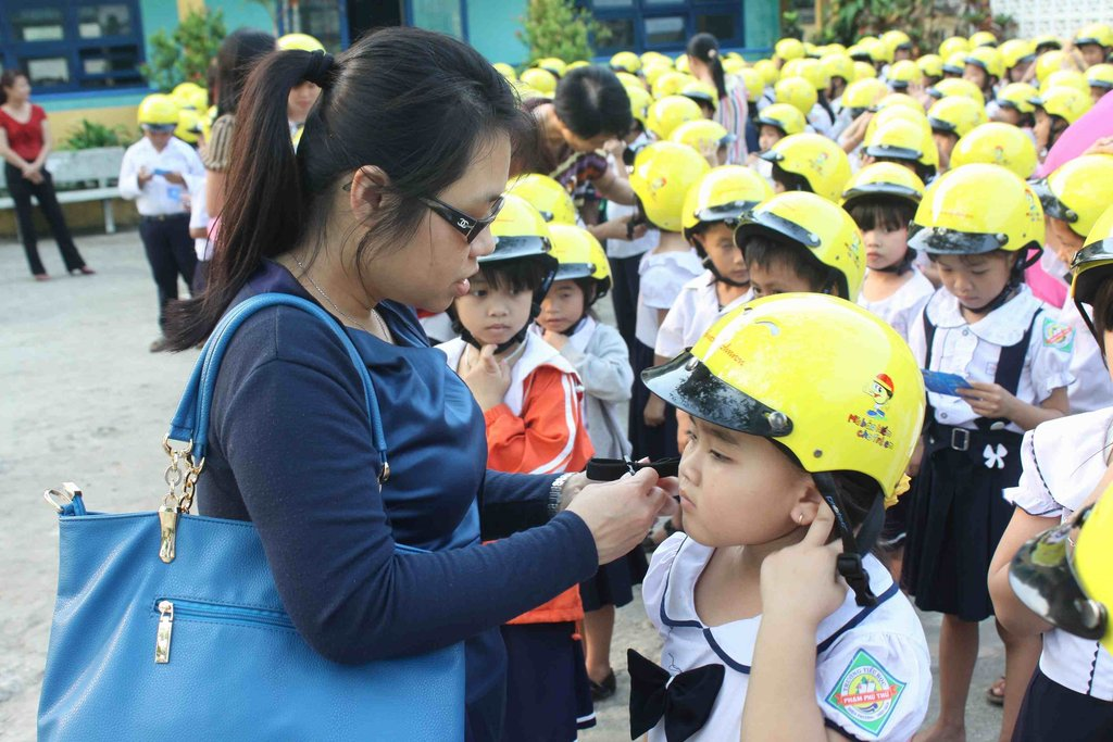 AIP Foundation teaches a child how to use a helmet