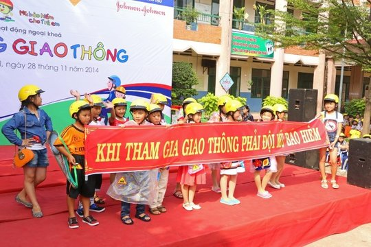 Students promote helmet safety messages on stage.