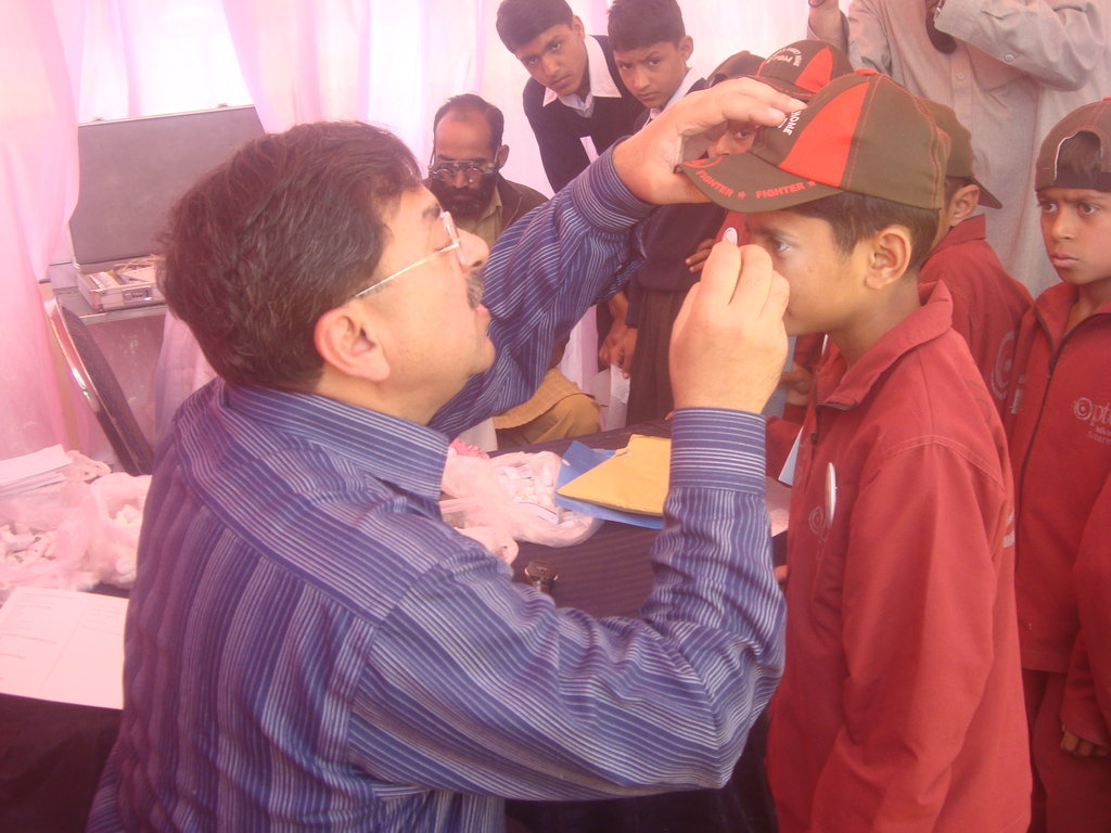 n this picture Doctor examining the eye sight of child with a view to find out any refractive error.