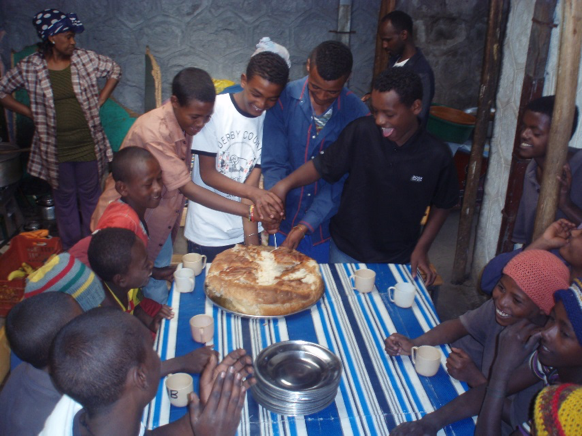 Departing boys cut bread to share with friends