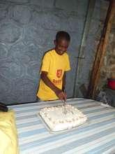 Teshome cuts the cake to celebrate