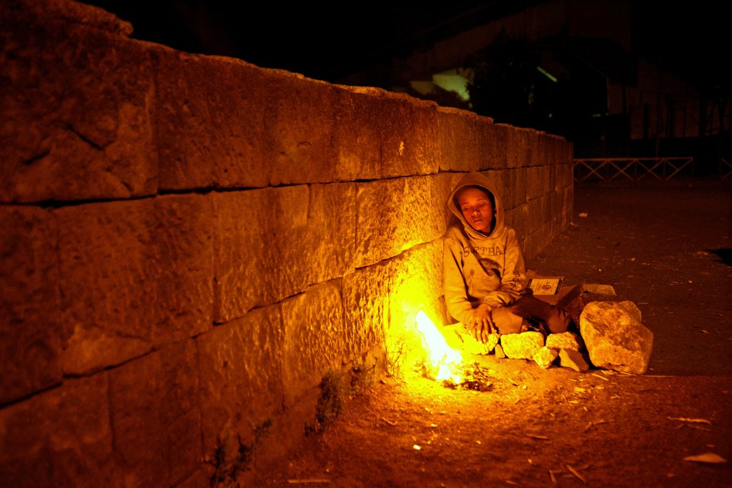 Young street child keeping warm by a fire. Photo taken in Addis Ababa, Ethiopia shows the harsh reality of a young child trying to keep safe at night time.