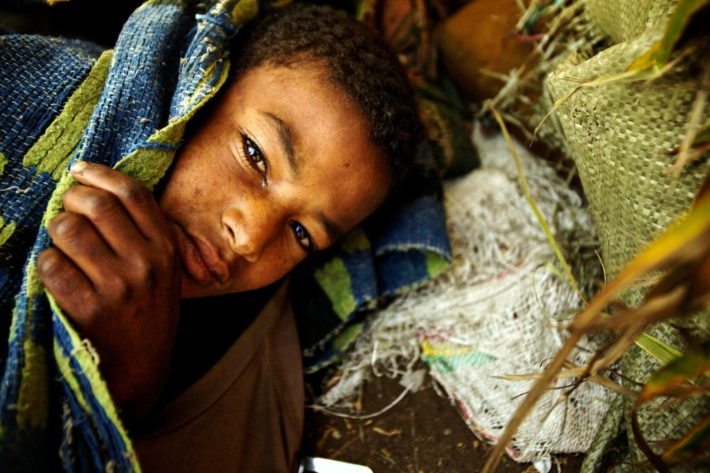 A boy trying to sleep on the central reservation of a road in Ethiopia