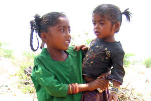 Girl child carrying her sibling