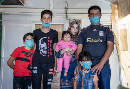 Manhal and his five children in a Jordan camp