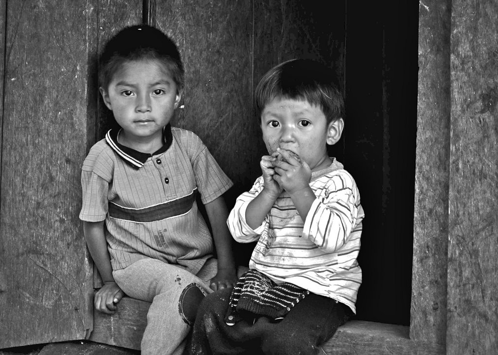 Two young boys sit in the doorway of their home as water distribution lines are installed. Water will now be delivered to their home, so they will not need to hike a hill to a storage tank to retrieve it.